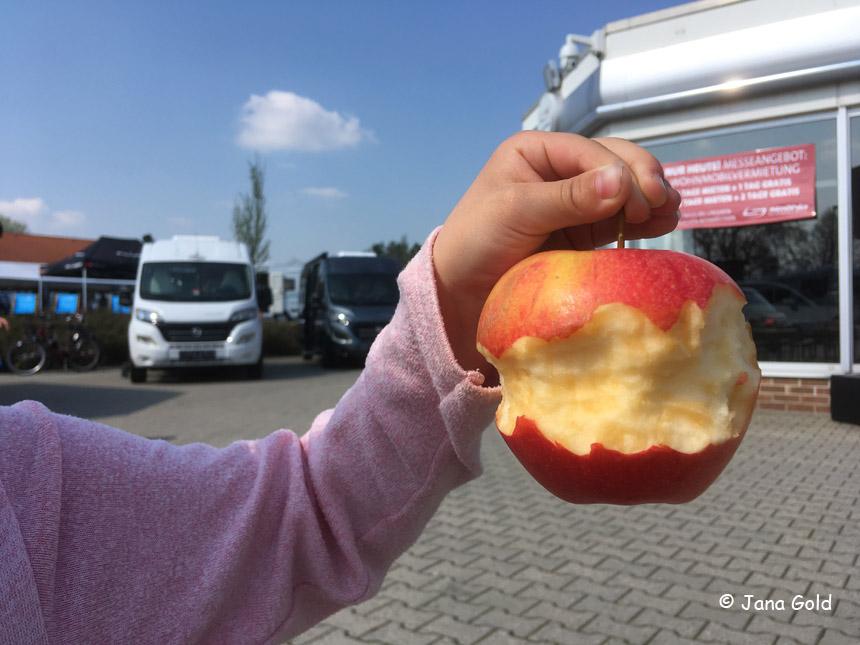 vor einem Wohnmobil und dem Autohaus Ströhla:wunderschöner rot-gelber, rundherum abgeknabberter Apfel