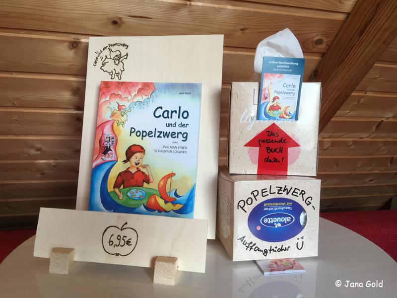 Das Buch im hübschen Präsenter zusammen mit der Popelzwerg-Auffangtücher-Box und hineingesteckten Lesezeichen
