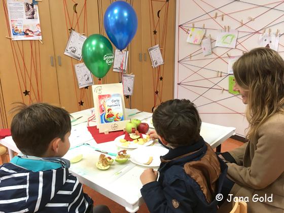 zwei Kinder sitzen mit ihrer Mutter am Tisch und betrachten ihre Apfelschiffchen